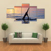 Sportive female doing yoga exercise on the beach standing on the sup board on the water in Multi panel canvas wall art