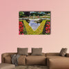 Exquisite fountain among the flower beds. Delightful landscaped wall art