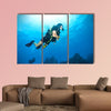 Young woman scuba diver exploring sea bottom. Underwater life with beautiful rocks and coral Multi panel canvas wall art