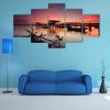 Beautiful sunset over wooden jetty with silhouette of man fishing, multi panel canvas wall art