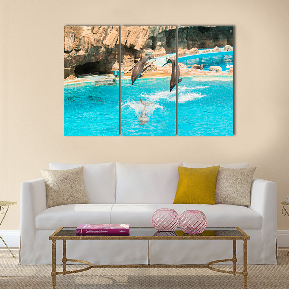 A group show of bottlenose dolphins performing a jump over water multi panel canvas wall art