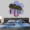 palm trees aligned in a desert with little water hexagonal canvas wall art