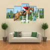 The rider on the red show jumper horse overcome high obstacles multi panel canvas wall art