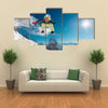 Girl is jumping with snowboard from the hill Multi panel canvas wall art