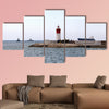 Red and white lighthouse near the fort of Christmas in Spain multi panel canvas wall art
