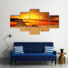 Camel caravan going through desert in front of pyramid at sunset Multi Panel Canvas Wall Art