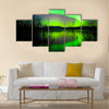 Intense Northern attractive lights (Aurora borealis) over Lake Laberge, Yukon Territory, Canada, with silhouettes of willows on lake shore Multi panel canvas wall art