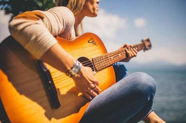 woman playing guitar outdoors beneath the summer sun