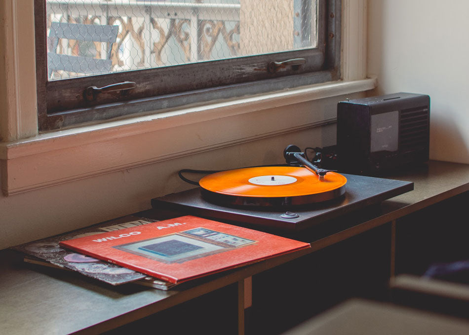 Simple record player by a window with Wilco album next to it