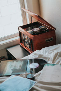 Modern record player beside a bed covered in vinyl records