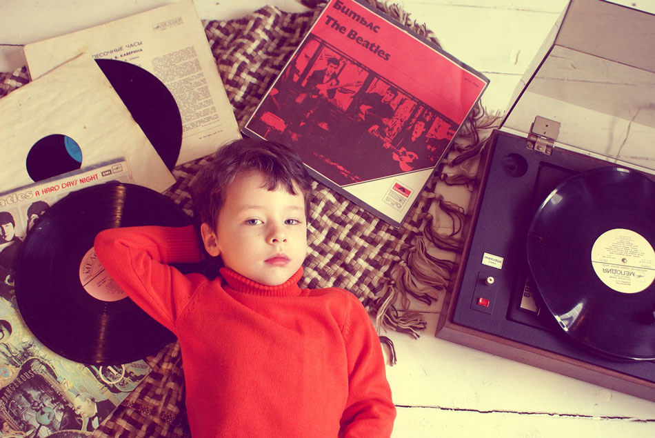 boy with red shirt laying on records