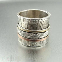 Wide sterling silver ring decorated with marked lines and swivel sterling silver, red and yellow gold bands.