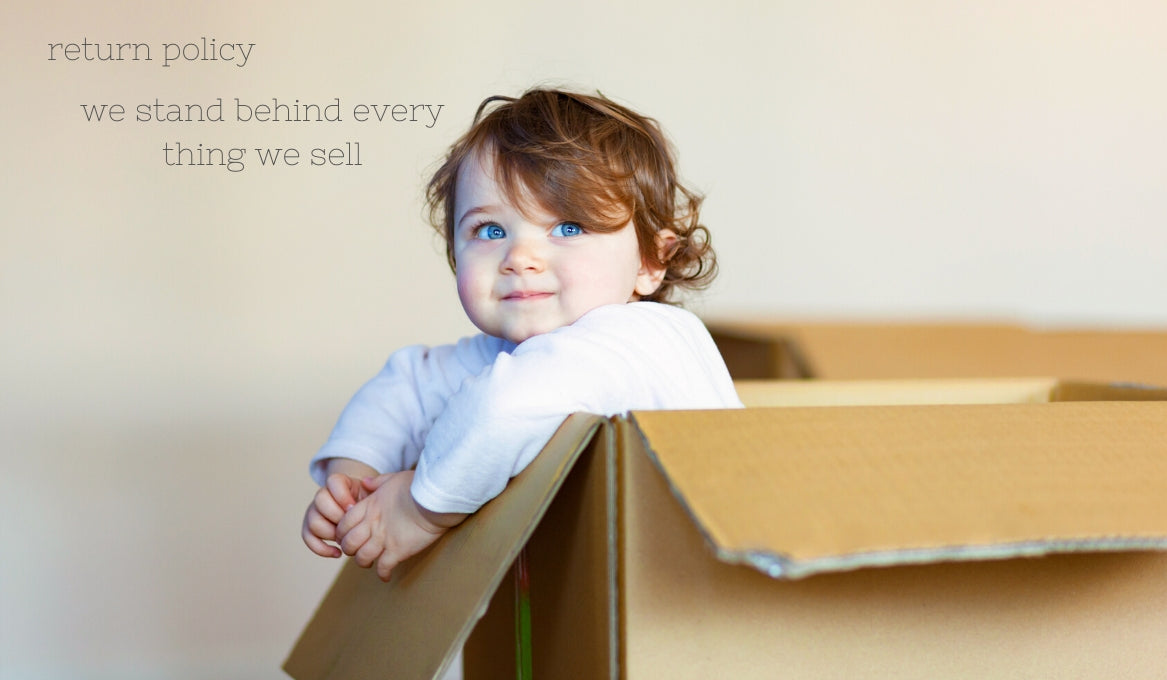 baby in cardboard box with blue eyes white merino clothes
