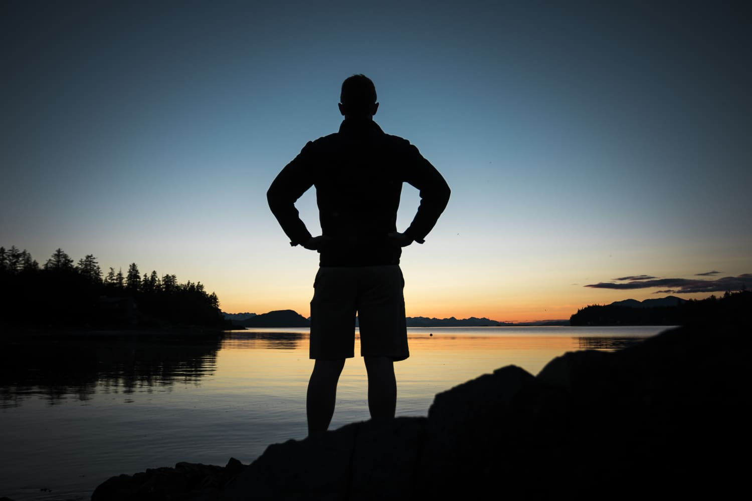 A silhouette of a man at the shore of a lake looking off into the distance at dusk