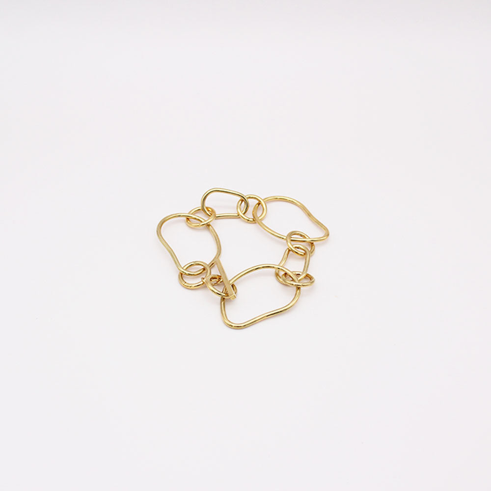 Gold chain link bracelet on a white background