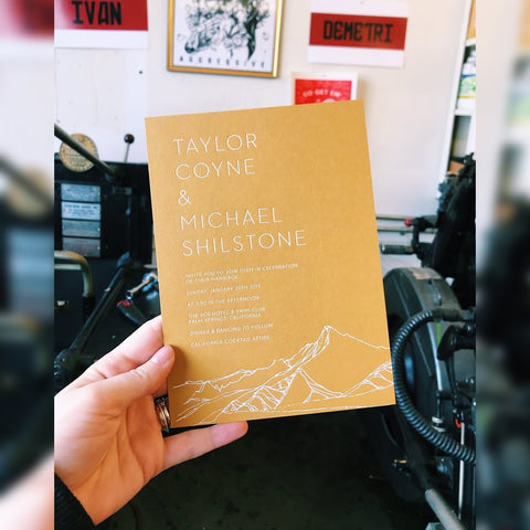 Taylor Coyne and Michael Shilstone White foil on yellow mustard paper wedding invitationwith mountainscape
