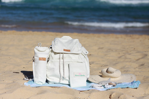 The Mama Qucha Baby Bundle in white - showing the Mama Qucha Beach Backpack and accessories at the beach