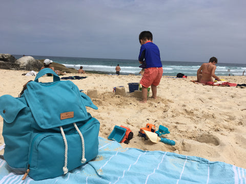The Mama Qucha Beach Backpack in turquoise shown at Tamarama beach in Sydney