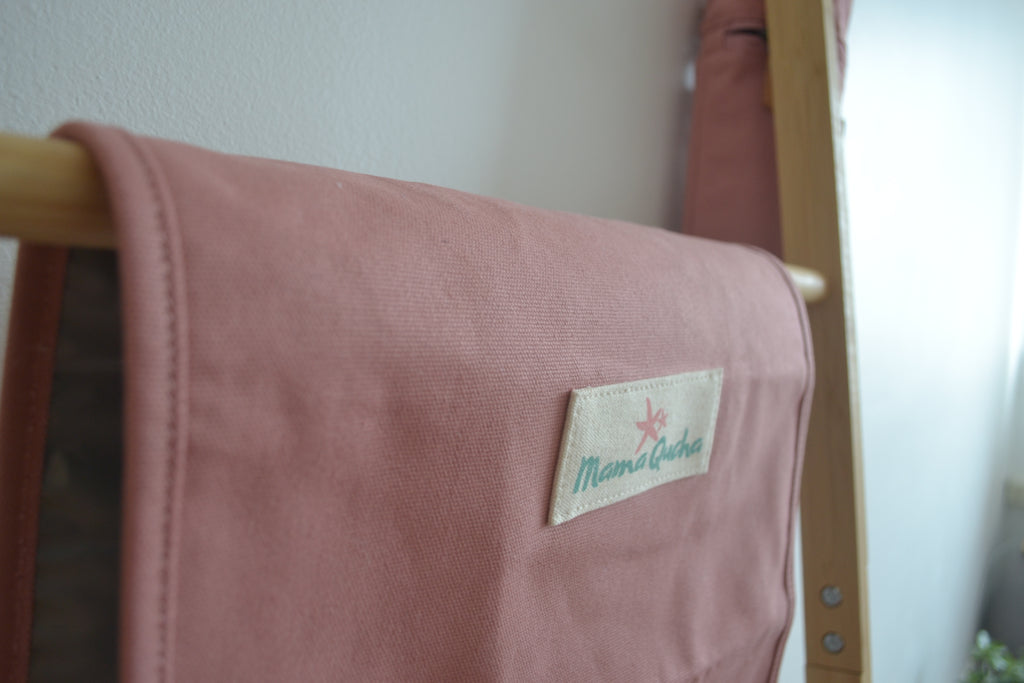 The Mama Qucha baby change mat in pink cotton when open and showing logo