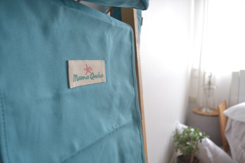 The Mama Qucha baby change mat in turquoise when open and showing close up of logo