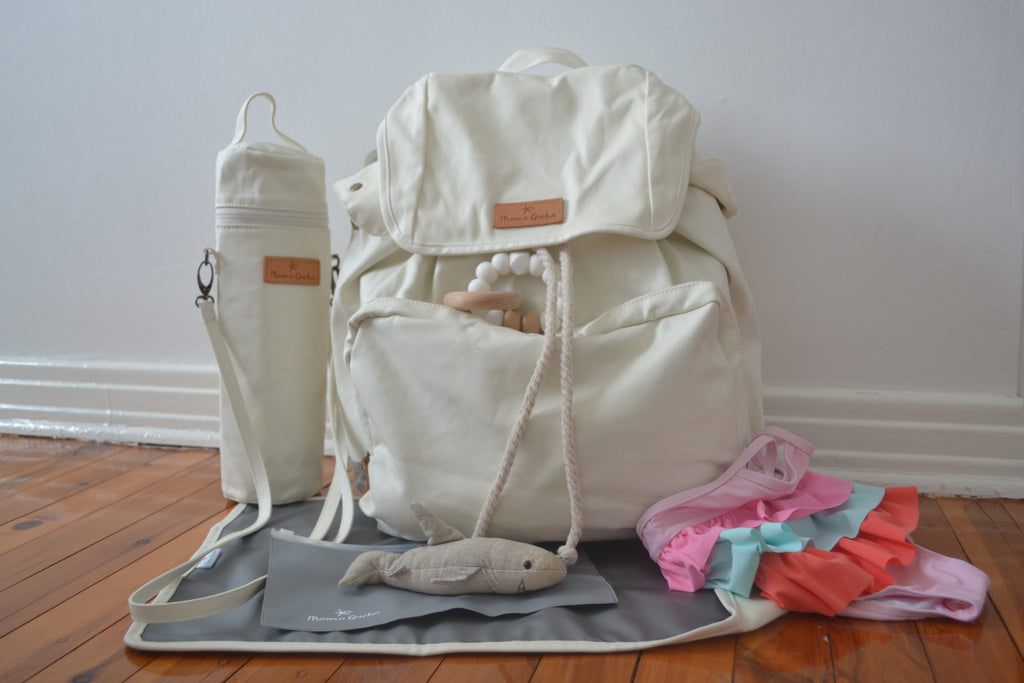 The Mama Qucha Baby Bundle | showing baby beach bag / diaper bag in white, baby bottle carrier, baby change mat and props