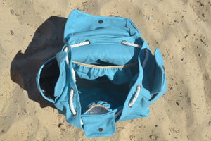 A top view of the Mama Qucha Beach Backpack (a baby beach bag) in turquoise photographed on the sand at the beach in Sydney Australia