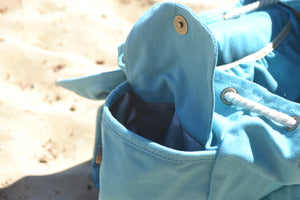 A view of the waterproof lined side pockets of the Mama Qucha Beach Backpack (a baby beach bag) in turquoise, photographed on the sand at the beach in Sydney Australia
