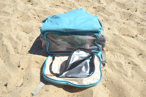 A view of the base of the Mama Qucha Beach Backpack (a baby beach bag) in turquoise, showing the waterproof base compartment and sand release; photographed on the sand at the beach in Sydney Australia
