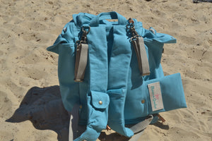 A back view of the Mama Qucha Beach Backpack (a baby beach bag) in turquoise photographed on the sand at the beach in Sydney Australia