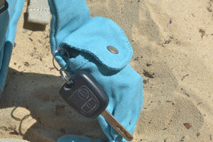 A view of the keys compartment on the straps of the Mama Qucha Beach Backpack (a baby beach bag) in turquoise, photographed on the sand at the beach in Sydney Australia
