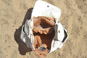 A top view of the Mama Qucha Beach Backpack (a baby beach bag) in white photographed on the sand at the beach in Sydney Australia