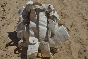 A back view of the Mama Qucha Beach Backpack (a baby beach bag) in white photographed on the sand at the beach in Sydney Australia