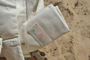 A close-up view of the back pocket of the Mama Qucha Beach Backpack (a baby beach bag) in white photographed on the sand at the beach in Sydney Australia
