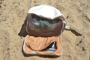 A view of the base of the Mama Qucha Beach Backpack (a baby beach bag) in white, showing the waterproof base compartment and sand release; photographed on the sand at the beach in Sydney Australia