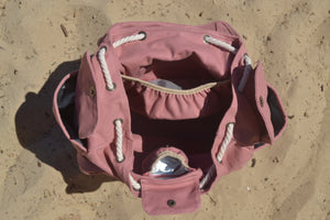 A top view of the Mama Qucha Beach Backpack (a baby beach bag) in pink photographed on the sand at the beach in Sydney Australia