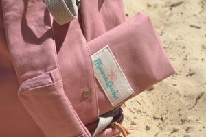 A close-up view of the back pocket of the Mama Qucha Beach Backpack (a baby beach bag) in pink photographed on the sand at the beach in Sydney Australia