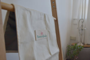 The Mama Qucha baby change mat in white waxed cotton showing close up of logo