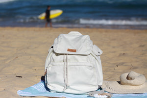 The Mama Qucha Beach Backpack (a baby beach bag) in white photographed on the sand at the beach in Sydney Australia