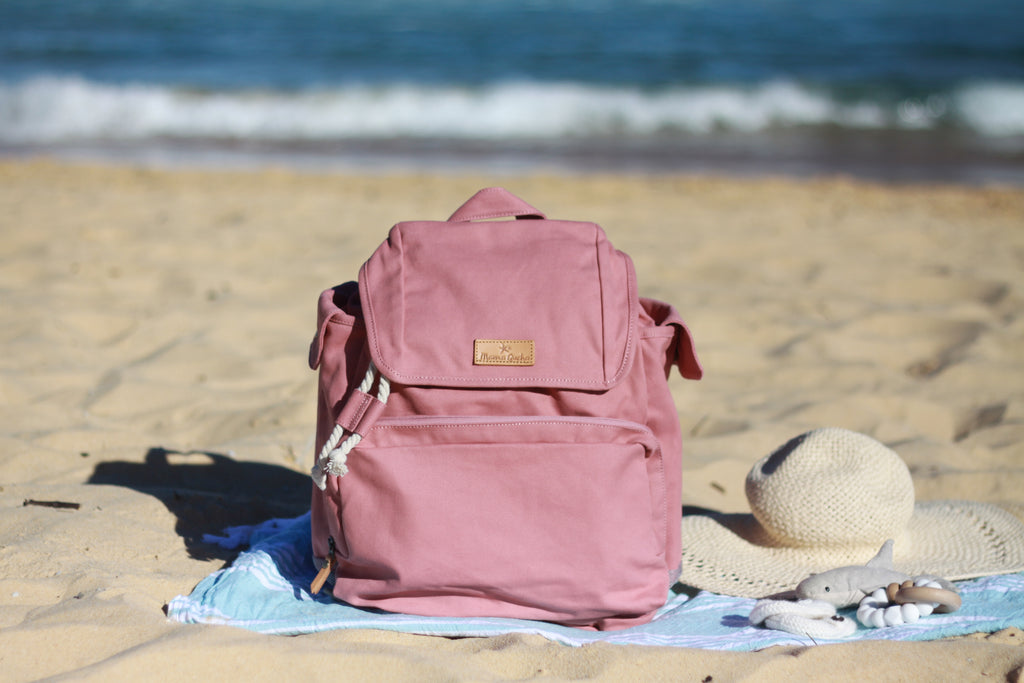 The Mama Qucha Beach Backpack (a baby beach bag) in pink photographed on the sand at the beach in Sydney Australia