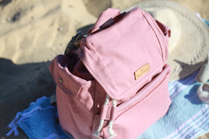 A close up top view of the Mama Qucha Beach Backpack (a baby beach bag) in pink photographed on the sand at the beach in Sydney Australia