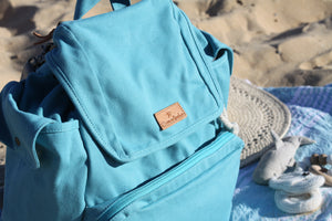 A close up top view of the Mama Qucha Beach Backpack (a baby beach bag) in turquoise photographed on the sand at the beach in Sydney Australia