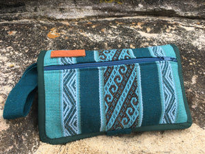 The Mama Qucha Cuzco Clutch | nappy clutch / diaper clutch in dark waves design showing outside zipped pocket shown on the sand