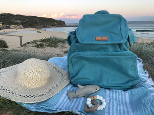 The Mama Qucha Nappy Backpack / baby beach bag in turquoise showing Mother&Baby Awards 2020 Shortlist logo - photographed on the sand at the beach in Sydney Australia