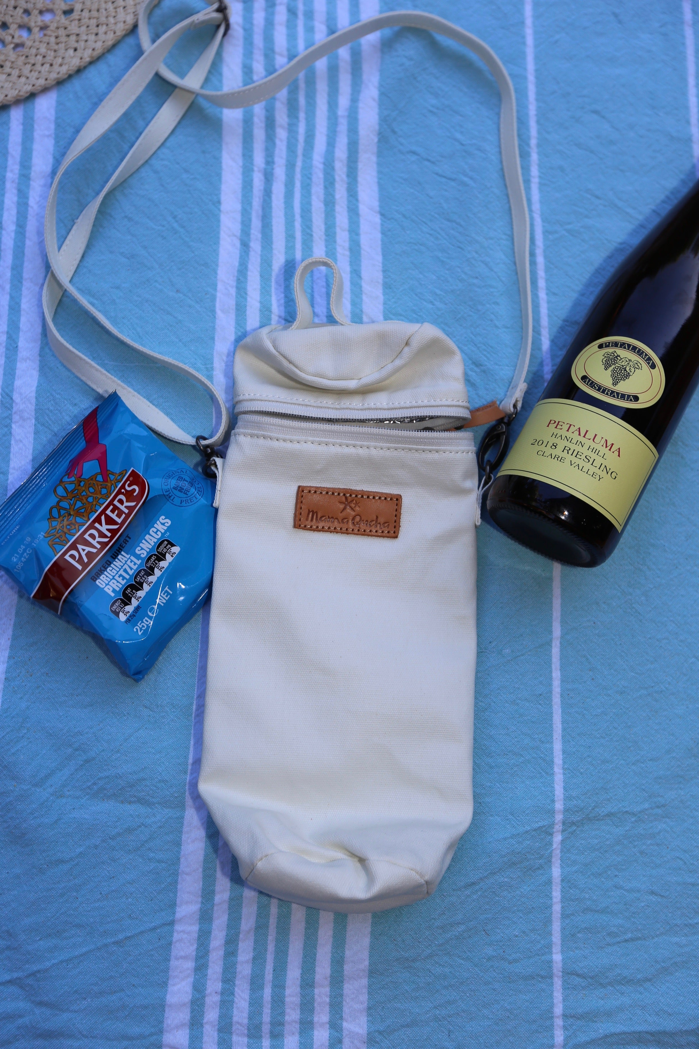 The Mama Qucha insulated bottle carrier / baby bottle holder in waxed white cotton show with props