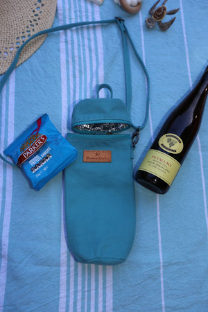The Mama Qucha insulated bottle carrier / baby bottle holder in turquoise cotton show with props