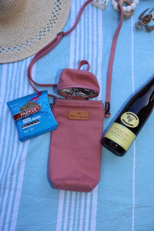 The Mama Qucha insulated bottle carrier / baby bottle holder in pink cotton show on towel with props