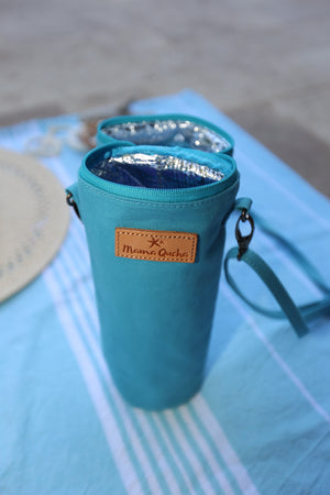 The Mama Qucha insulated bottle carrier / baby bottle holder in turquoise cotton show open and on a towel