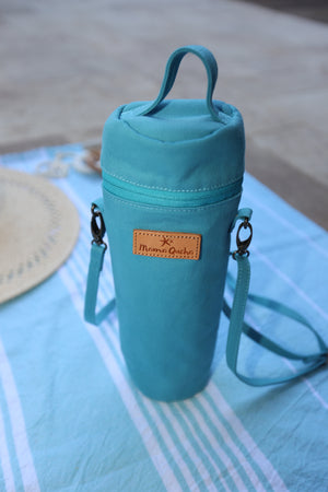 The Mama Qucha insulated bottle carrier / baby bottle holder in turquoise cotton show closed and on a towel