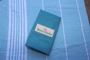 The Mama Qucha baby change mat in turquoise when folded and showing logo
