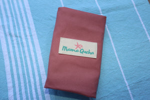 The Mama Qucha baby change mat in pink cotton when folded and showing logo